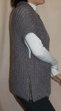 Жилет женский вязаный, выполнен спицами. Жилет - универсальная незаменимая деталь в гардеробе любой женщины. Данная модель выполнена спицами из 100%-ной шерстяной пряжи, по бокам декорирован молниями.
