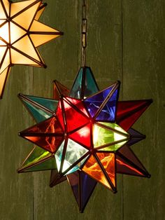 brightly colored glass moravian star pendant light hung against a weathered-look, green, wood-slat wall