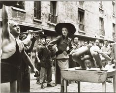 Elise Daniels with Street performers, suit by Balenciaga, Le Marais, Paris, August 1948. Richard Avedon
