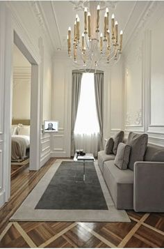 Elegant neutral room with muted grays, whites, and creams and a chandelier as a statement piece