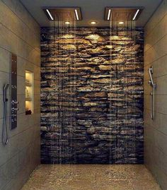 This stunning modern master bathroom featuring a natural stone wall and rain shower heads, will leave you feeling like your showering under a magnificent waterfall. #luxurious #design #interiordesign #interiorstyle #homedecor #luxury #lifestyle #style  #remodeling #renovation #bathroom #bathroomideas #bathroomdesign