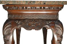 """Detail ~ 19thC Irish Chippendale Center Table ~ A wonderfully carved Irish Chippendale mahogany center hall table (or server), the long sides centered with large growling lions heads below greek key and egg and dart moldings; the four legs with shell carving to the tops, tapering to large hairy paw feet; topped with a wonderful 'green pink' marble slab; Irish mid-19thC.     Dimensions: (marble 44"""" x 24""""), table height 32.5"""" / Three Centuries Shop"""
