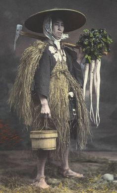 Posed photograph of Japanese farmer in straw coat and hat. Late 19th century, Japan. Hand-colored photo