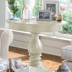 Showcasing a turned pedestal base and lovely linen-hued finish, this elegant wood end table is perfect catching keys and mail in your foyer or displaying a l...