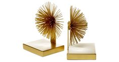 "Frame your favorite covers with a sculptural touch. These starburst bookends are glamorous in gold.Founded by Bob and Bobbie Gottlieb, the original ""two"" in the company name, Two's Company is a..."
