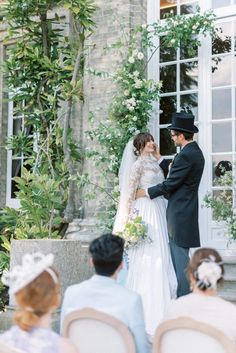 hedsor house spring summer wedding ceremony in the garden; floral installation and flower pillar with david austen roses; bride wearing a marchesa longsleeves white lace wedding gown with silk brocade full ball gown skirt; groom wearing a black top hat with black dior long suit coat and pinstripe trousers   Photo by London and Newcastle UK based light bright and airy Filipina wedding photographer Cristina Ilao