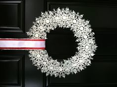 My attempt at the snowflake wreath using a wire coat hanger, 4 packs of dollar store glitter snowflakes and some ribbon