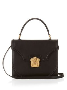 An investment in Alexander McQueen's black calf-leather satchel is an investment in timeless elegance. The smart boxy silhouette is perfectly offset by the opulent 17th-century inspired gold-tone brass flower clasp with amber-crystal embellishments. Let the accent really pop against an all-black ensemble. | Available at MATCHESFASHION.COM