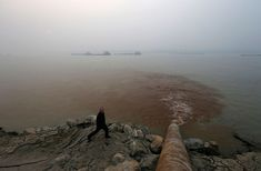 This photo shows a man walking past a pipe that is discharging waste water into the Yangtze River. The waste water seen here is being discharged from a paper mill in the Anhui province. This photo shows how pollution diminishes the quality of water as it is continuously added to different bodies of water.