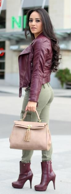 Dark cranberry leather jacket, army green pants, matching cranberry colored booties and a beige tassel purse.