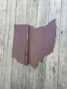 """This Ohio wall hanging is hand cut from old salvaged tin.  It is sealed with shellac to give it a beautiful sheen to it.  The state measures 12 1/2"""" wide and 14"""" tall.      This item is available in 3 different options:      1.  you can purchase just the tin state, no hangers or attached to wood, $20      2.  Attached to a whitewashed distressed 3/4"""" pine board (see picture of state of Texas), $45      3.  Attached to burlap wrapped pine board (see picture of the state of Iowa), $45…"""