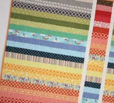 It looks like she sewed a rainbow sash quilt, cut out a strip and turned it upside down, bordered it with white and sewed it all back together...clever!