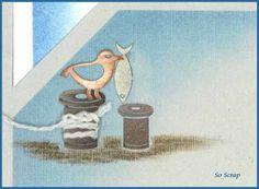 Des figurines dentelles bobines sont coupées pour former des bites d'amarrage. L'une d'elle est entourée d'une cordelette. Un oiseau qui tient dans son bec un poisson (toujours en figurines dentelle) est posé sur celle-ci. L'assise de la saynète est ravaillée au crayon craie.