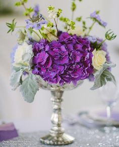 Create a romantic table centerpiece with a silver mercury glass pedestal bowl filled with silk flowers, like rich purple hydrangess and delicate cream roses.  Find everything you need to create this look for less at Afloral.com.