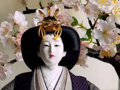 深い色合いの大島紬が落ち着きを表現し、桜の木と掛け軸が雛人形に彩りを添える立ち雛親王飾り