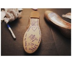 Must-Take Photo: A still life of the bride's shoes. This bride had her bridesmaids share their best wishes on her soles, in blue ink no less.