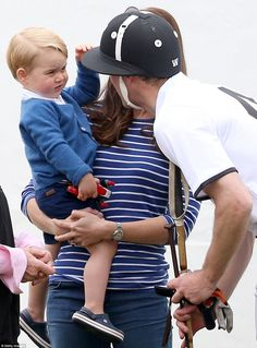 Well played! Prince George tentatively touches his father Prince William's helmet before pulling his hand away
