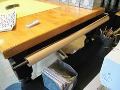 Curtin rods attached to table allows you to hang wrapping paper, butcher paper etc.
