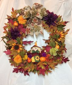 "Scarecrow fall wreath. Oak leaves, sunflowers, and mums on 18"" vine form. Stuffed fabric scarecrow at base. Oak leaf bow.  Chenille hanger. by KhQualityCreations on Etsy"