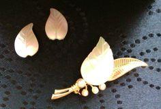 Schönes Set Blätter aus Perlmutt. Ohrclips 2,3 cm lang und 1,4 cm breit. Die Brosche ist zudem mit vier Perlchen verziert. Brosche 6,5 cm lang und 2,8 cm breit. Die Ohrclips sind älter als die...