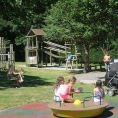 Un grand parc de jeux gazonné avec toboggans, tourniquet...