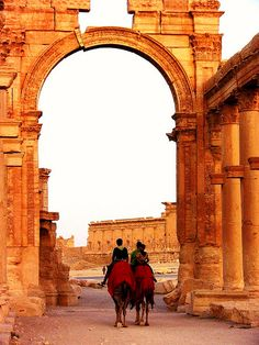 Camel riders crossing under the Arch of Hadrian in Palmyra, Syria