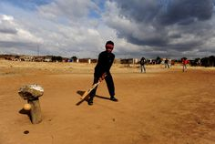 Kids Play Cricket In Botshabelo.  A young boy misses the ball while enjoying a game of cricket with his friends on June 21, 2009 in Botshabelo near Bloemfontein, South Africa. The large black settlement of Botshabelo, set up by the then apartheid government, has a population of about one million inhabitants.