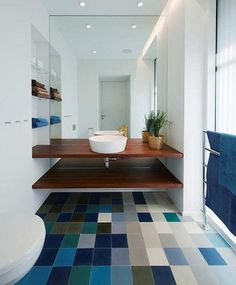 Using different colored tiles in same complementary colors create a dynamic effect in this sleek bathroom.