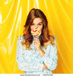 Portrait of a happy student girl holding sweet candy over yellow background