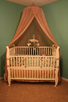 Wooden White Baby Crib with Amazing Pattern Bedding complete with the Hanging Toy Accessories and Transparent Pink Curtain for Baby Nursery Crib Decorating with Canopy