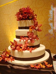 Elegant cream and brown four-tier wedding cake with burnt orange flowers. Beautiful fall/winter colors for a wedding cake!