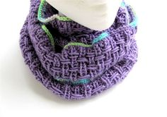 A true lilac shade is like no other and is shown off in this one of a kind cowl. An interesting stitch done in a lilac acrylic and cotton yarn with a bit of a surprise in the hidden lines of another variegated yarn make this a truly unique cowl. Shades of green, blue, lilac and cream peek out between the three blocks of lilac. it measures 9 (22.5cm) wide and has a soft drape. It can be worn singly or doubled and will surely be a show stopper!  Machine wash cold and lay flat to dry.   It was…
