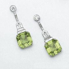 PAIR OF DIAMOND AND PERIDOT PENDANT-EARRINGS Anchored by 2 emerald-cut peridots weighing approximately carats, suspended from fringes of round and baguette diamonds weighing approximately carats, mounted in platinum. Art Deco Jewelry, High Jewelry, Jewelry Gifts, Jewelry Design, Geek Jewelry, Jewelry Trends, Jewelry Necklaces, Jewellery, Antique Jewelry