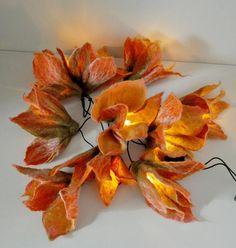 Eine Lichterkette mit 10 handgefilzten Blüten gestaltet. Die Blüten sehen aus, wie die Blüten einer Lilie in den Farben Orange, Pfirsich und Weiß. Das