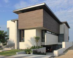 Casa moderna con colores tierra y garage en la parte baja.