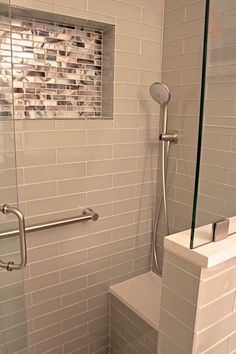 Renovated Bathroom, handicap acessibble with beautiful tile mosaics and subway tile. The ledge and seat are made out of Cambria quartz stone in Newport. All designed and custom built by Florida Bath & Surfaces