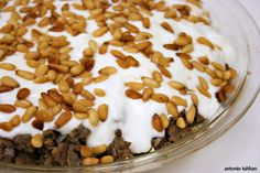 Middle Eastern recipe (Fateh). Toasted bread, meat, chickpeas with yogurt sauce and pine nuts topping (can also use toasted almonds slices instead of pine nuts).