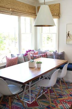 Chic meets boho when a wooden table top is accessorized with a single orchid and an array of printed pillows.