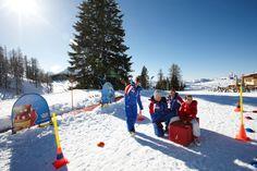 Spielen im Schnee. Urlaub im Hotel Sonnhof im Alpendorf. Zauberteppich vorm Hotel im Salzburger Land Österreich
