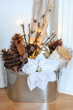 Christmas Decorations: Take a bucket fill it with birch, pine cones, ornaments, twig lights, cinnamon sticks wrapped in brown satin ribbon, and a white poinsettia flower.
