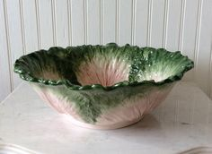 This is a beautiful Fitz & Floyd Decorative Serving Bowl. Done in the pink & vivid green cabbage leaf design. Excellent Vintage Condition!!! Ready for displaying proudly on table as a centerpiece, in hutch or island kitchen decor! Hard to find bowl, great gift for anyone who collects this gorgeous pattern. Stamped on bottom FITZ & FLOYD along with sticker which reads handcrafted in Malaysia. Done in colors of creamy white, pink & green. ( no chips or cracks). Convo for any questions you…