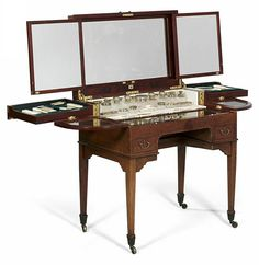 """Outstanding lady's dressing table,  According to the brass plaque produced by the English firm """"H. GREAVES. LTD, NEW St BIRMINGHAM"""" circa 1900. Made in mahogany, of almost perfect execution, a simple cube form set on conical legs with casters, two external drawers, a hinged top with three-part mirror, various compartments for utensils, glass shelves and a leather inset for jewellery, various containers partly in ivory, glass and silver. Measurements when open 145 x 178 x 72 cm."""