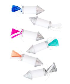 "- Set of 6 rockets - Paper - 4"" long - Glitter Details - Each Rocket contains confetti, hat, fortune & moustache"