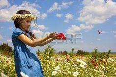 Niña en el campo con flores silvestres. Foto de archivo.