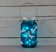 Blue and white dragonfly Mason jar. A quart-sized Mason jar was tinted blue and then white dragonflies were had painted onto the blue surface. The jar is filled with a string of tiny battery-operated Moon lights. The battery pack requires two coin batteries (included). The batteries are replaceable for additional glow time.
