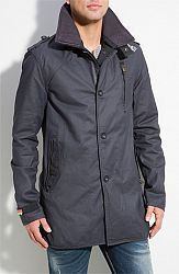 Vertical zip and snap-flap pockets streamline a stiff, modern fitting trench coat topped by an oversized rib-lined stand collar outfitted with removable metal collar stays and snap-tab closure....