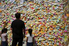 A man and girls read messages left by pro-democracy protesters outside the government headquarters in Hong Kong on October 12, 2014. (Reuters/Bobby Yip)