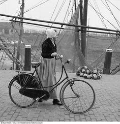Vrouw in klederdracht loopt op 7 april met haar fiets aan de hand langs de vissershaven van Veere, waaruit, vanwege de afsluiting door de Veerse Gatdam, voor het laatst de vissersvloot vertrekt (1961) #Zeeland #Walcheren