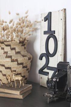 Vintage camera, old books, chippy piece of siding and numbers turned down home décor vignette... | 'Thrift Store Swap Makeover'