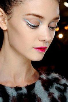 Een cateye bij Dior, maar niet op de klassieke manier. Raf Simons wilt er een moderne versie van. Dus tekent visagiste Pat McGrath niet alleen boven het ooglid een zilveren lijntje, maar ook onder de ogen, en een smal streepje in de bovenhoek.
